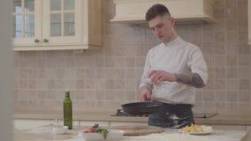 El hombre joven en uniforme del cocinero pone la sal en la cacerola del fryng y lanza para arriba la carne en una sartén Un cocin metrajes