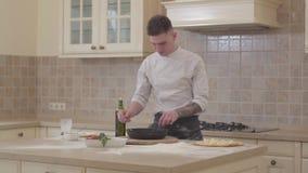 El hombre joven en uniforme del cocinero toma el sartén con la carne recientemente asada de la estufa y lo pone en base de la piz metrajes