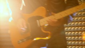 El hombre joven en vaqueros toca la guitarra en el primer ligero trasero brillante almacen de metraje de vídeo