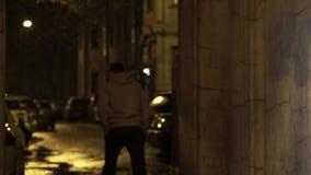 El hombre joven en vidrios camina en pasillo y da vuelta lejos en la noche almacen de metraje de vídeo