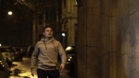El hombre joven en vidrios corre en pasillo y sonríe en la noche almacen de metraje de vídeo