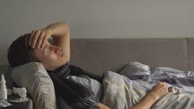 El hombre joven enfermo está tomando temperatura y está tosiendo en su cama Las píldoras y las medicaciones de la abundancia está metrajes