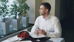 El hombre joven enojado bien vestido está esperando a su novia en restaurante, usando smartphone, joyero de apertura y metrajes