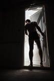 El hombre joven entra en la puerta de abertura de oscuridad imagenes de archivo