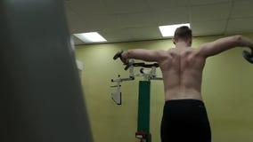 El hombre joven entrena a sus hombros con pesas de gimnasia en el gimnasio