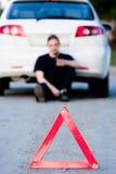 El hombre joven envía los sms que se sientan por un coche blanco fotografía de archivo