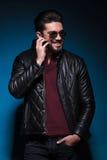 El hombre joven es de risa y de rasguño de su barba Imagen de archivo libre de regalías