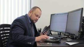 El hombre joven es trabajo, sentándose en la tabla en oficina moderna almacen de video