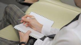 El hombre joven escribe en el cuaderno, sentándose en oficina moderna metrajes