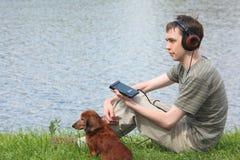 El hombre joven escucha música se sienta con el perro Imagenes de archivo