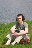 El hombre joven escucha música se sienta con su perro Fotografía de archivo libre de regalías