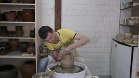 El hombre joven esculpe productos de la arcilla almacen de metraje de vídeo