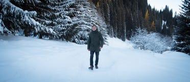 El hombre joven está caminando en montañas del invierno Foto de archivo libre de regalías
