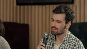 El hombre joven está cantando una canción en club Imágenes de archivo libres de regalías