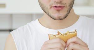 El hombre joven está comiendo la hamburguesa en casa, la boca y las manos con el primer de la comida almacen de metraje de vídeo