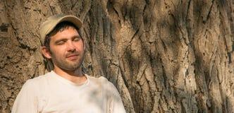 El hombre joven está descansando cerca de un árbol Imágenes de archivo libres de regalías