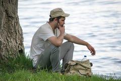 El hombre joven está descansando cerca de un árbol en la orilla del río Fotos de archivo libres de regalías