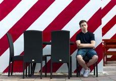 El hombre joven está descansando sentarse en una tabla en un café Imágenes de archivo libres de regalías