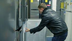 El hombre joven está eligiendo un refrigerador en una tienda Él está abriendo las puertas, mirando dentro almacen de metraje de vídeo