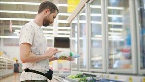 El hombre joven está examinando el paquete con las verduras congeladas en un pasillo del supermercado almacen de metraje de vídeo