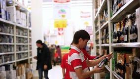El hombre joven está haciendo compras en supermercado choosing almacen de metraje de vídeo
