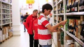 El hombre joven está haciendo compras en supermercado choosing metrajes