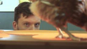 El hombre joven está intentando coger un pollo vivo