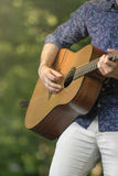 El hombre joven está jugando en su guitarra foto de archivo