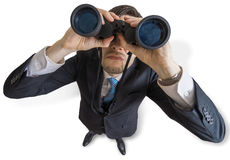 El hombre joven está mirando con los prismáticos usted Aislado en el fondo blanco Imagen de archivo