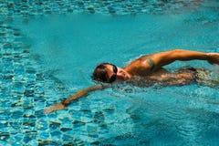 El hombre joven está nadando en un agua transparente de una piscina Imagenes de archivo