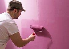 El hombre joven está pintando la pared con el rodillo fotografía de archivo libre de regalías