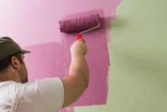 El hombre joven está pintando la pared con el rodillo imágenes de archivo libres de regalías