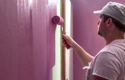 El hombre joven está pintando la pared con el rodillo imagenes de archivo