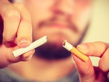 El hombre joven está rompiendo un cigarrillo Fotos de archivo