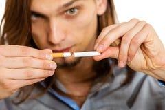 El hombre joven está rompiendo un cigarrillo Fotografía de archivo libre de regalías