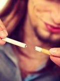 El hombre joven está rompiendo un cigarrillo Imágenes de archivo libres de regalías