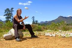El hombre joven está sacudiendo una roca fotografía de archivo libre de regalías
