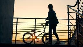 El hombre joven está saltando de las verjas y está saliendo con su bici durante puesta del sol metrajes