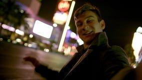El hombre joven está sosteniendo la cámara delante de sí mismo y está invitando todos a Las Vegas almacen de video