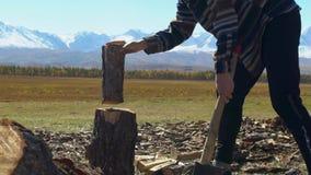 El hombre joven está tajando la madera en montañas máximas nevosas almacen de video