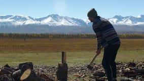 El hombre joven está tajando la madera en montañas máximas nevosas almacen de metraje de vídeo