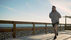 El hombre joven está tensando los músculos de sus piernas que hacen posiciones en cuclillas al aire libre en salida del sol almacen de metraje de vídeo