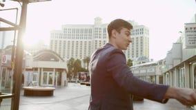 El hombre joven está tirando un vídeo sobre Las Vegas usando un palillo del selfie mientras que camina almacen de metraje de vídeo