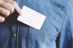 El hombre joven está tomando una tarjeta en blanco en el bolsillo de su camisa foto de archivo