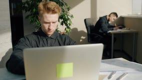 El hombre joven está utilizando el ordenador portátil durante día laborable en oficina moderna almacen de video