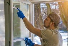 El hombre joven está utilizando un trapo y un enjugador mientras que limpia ventanas Fotos de archivo libres de regalías