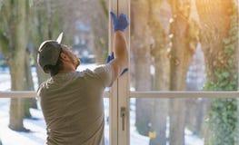 El hombre joven está utilizando un trapo y un enjugador mientras que limpia ventanas Fotografía de archivo libre de regalías
