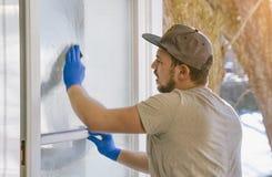 El hombre joven está utilizando un trapo y un enjugador mientras que limpia ventanas Fotografía de archivo