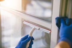 El hombre joven está utilizando un trapo y un enjugador mientras que limpia ventanas Imágenes de archivo libres de regalías