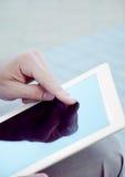 El hombre joven está utilizando una tableta Imagenes de archivo